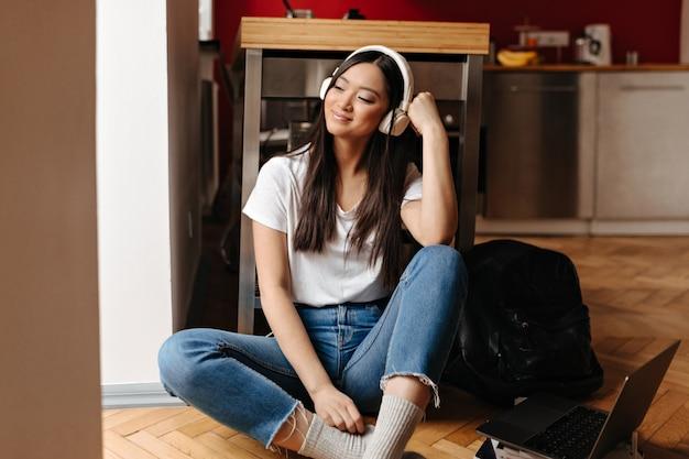 Ciemnowłosa kobieta w białej bluzce i dżinsowych spodniach słucha muzyki w słuchawkach