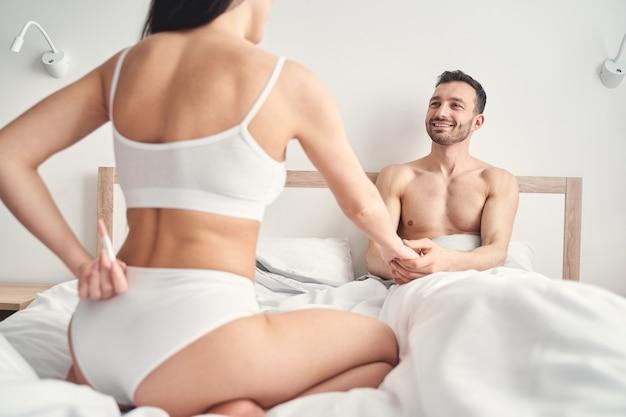 Ciemnowłosa kobieta w bieliźnie siedząca przed mężem w łóżku z testem ciążowym
