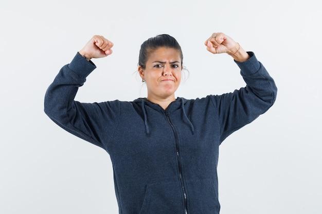 Ciemnowłosa kobieta w kurtce unosi ramiona, pokazując mięśnie i wyglądając na potężnego