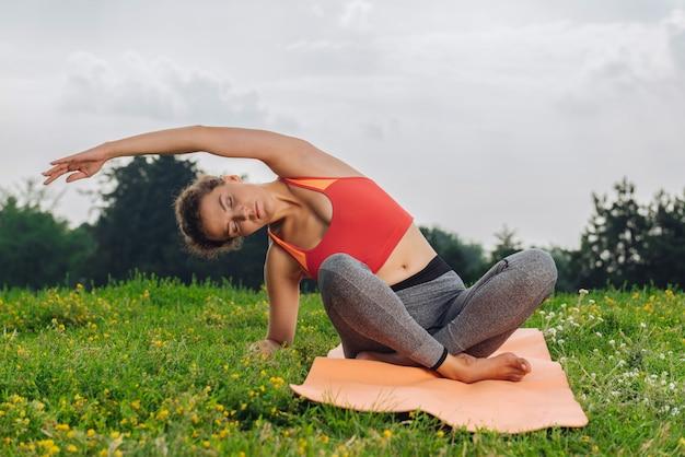 Ciemnowłosa kręcona kobieta lubi jogę, siedząc w pozie rozciągającej i ciesząc się spokojną atmosferą