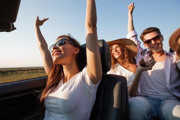 Ciemnowłosa młoda kobieta ubrana w białą koszulkę siedzi z przyjaciółmi w czarnym kabriolecie w letni dzień. .