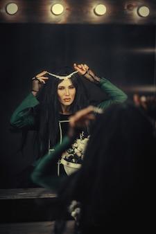 Ciemnowłosa modelka pozuje w ciemnym pokoju z lustrem