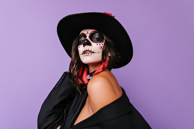 Ciemnowłosa namiętna dama z halloweenową twarzą, trzymająca czarny kapelusz.