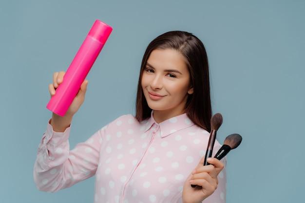 Ciemnowłosa pozytywna kobieta trzyma lakier do włosów i dwa pędzle kosmetyczne