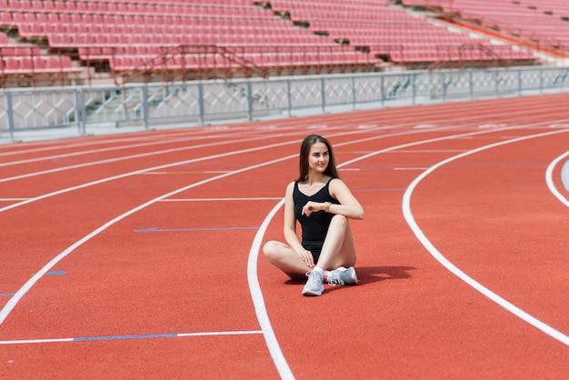 Ciemnowłosa trenerka stoi na czerwonym bieżni stadionu, ubrana w sportowy strój.