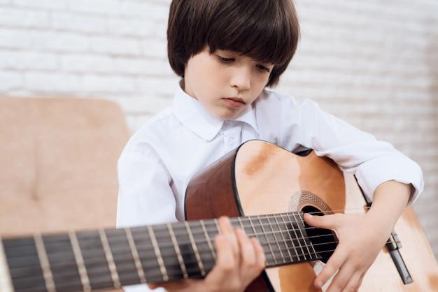 Ciemnowłosy chłopak w białej koszuli gra na gitarze.