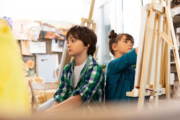 Ciemnowłosy chłopiec nudzi się na lekcji plastyki w szkole