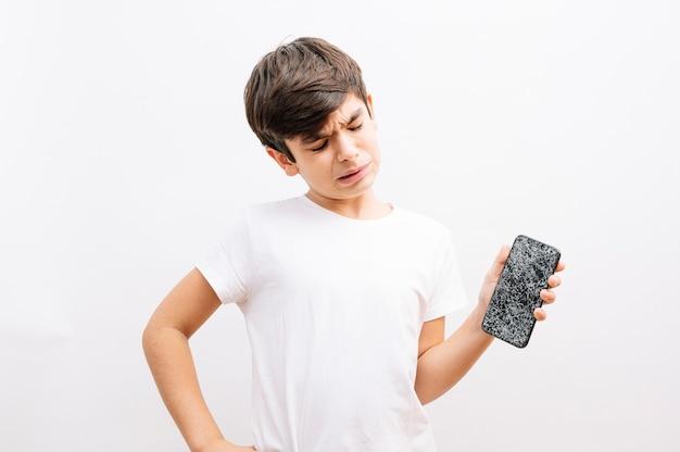 Ciemnowłosy chłopiec trzymający uszkodzony smartfon z płaczącym wyrazem twarzy