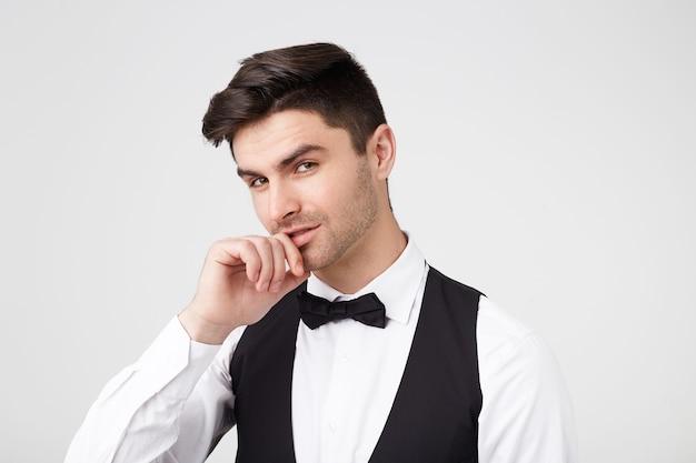 Ciemnowłosy facet z modną fryzurą, jasnym włosiem, ubrany w czarny garnitur z muszką, trzyma rękę w pobliżu ust