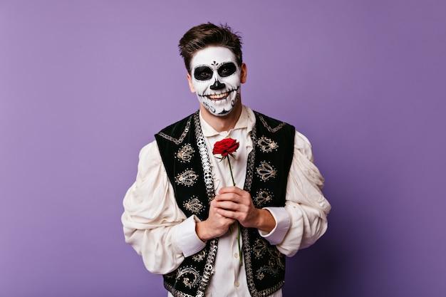Ciemnowłosy facet z pięknym uśmiechem w świetnym nastroju, pozuje na odizolowanej ścianie. zdjęcie meksykanina z grafiką twarzy i różą w dłoniach.