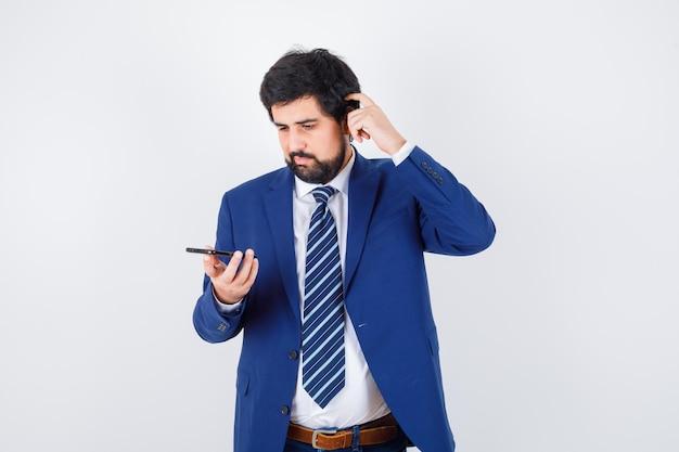 Ciemnowłosy mężczyzna patrząc na telefon drapiąc się po głowie w białej koszuli, granatowej marynarce, krawacie, widok z przodu.