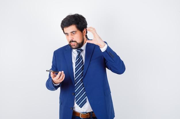 Ciemnowłosy mężczyzna patrząc na telefon w białej koszuli, granatowej marynarce, krawacie i patrząc agresywnie, widok z przodu.
