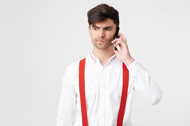Ciemnowłosy mężczyzna rozmawiający przez telefon komórkowy, ubrany w koszulę i czerwone szelki wygląda na rozczarowanego