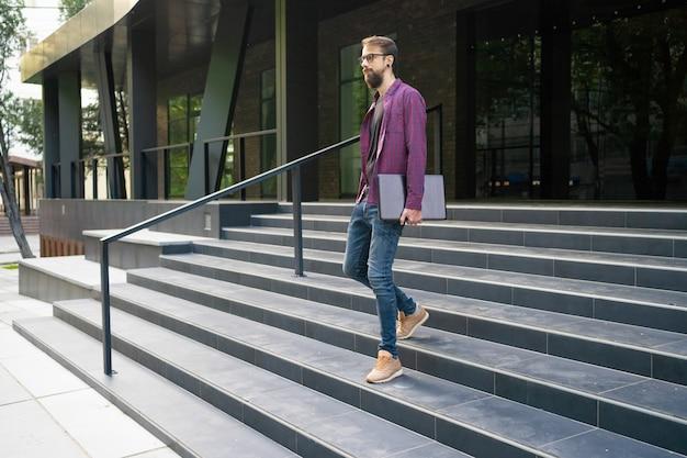 Ciemnowłosy mężczyzna schodzi po schodach i trzyma laptopa