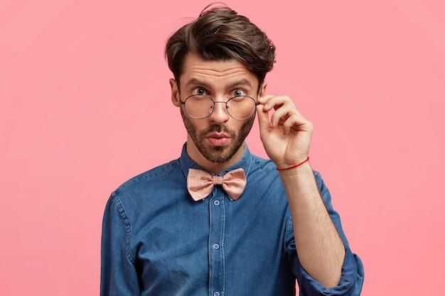 Ciemnowłosy mężczyzna ubrany w różową muszkę i dżinsową koszulę