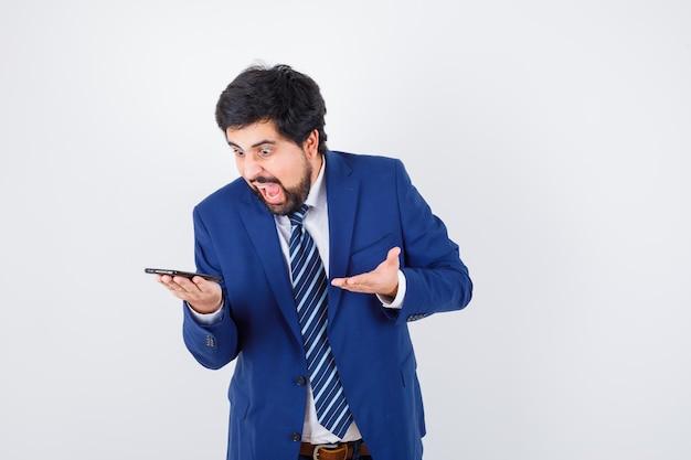 Ciemnowłosy mężczyzna w białej koszuli, granatowej marynarce, krawacie krzyczy podczas rozmowy przez telefon i wygląda na przerażonego, widok z przodu.