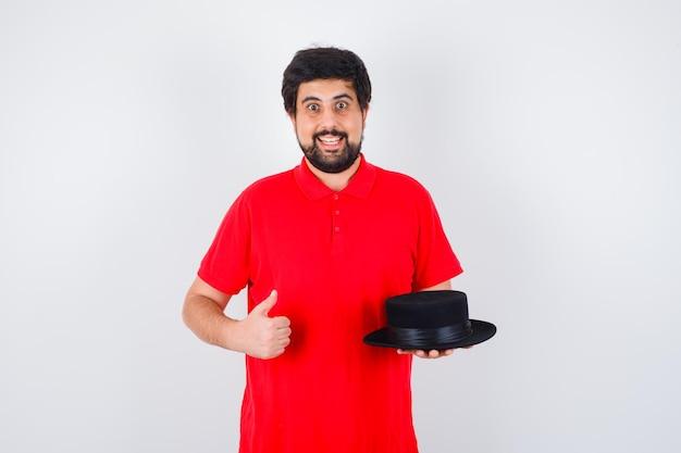 Ciemnowłosy mężczyzna w czerwonej koszulce trzymającej kapelusz pokazując kciuk do góry i patrząc zadowolony, widok z przodu.