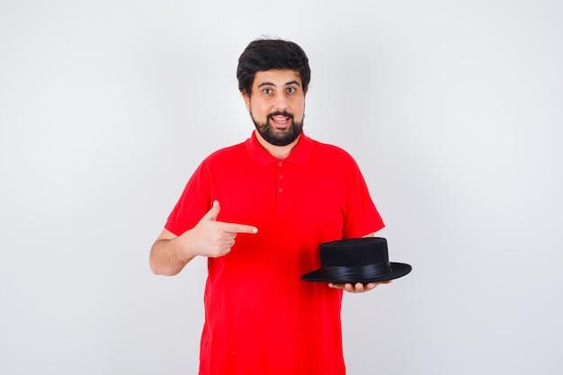 Ciemnowłosy mężczyzna w czerwonej koszulce wskazujący na kapelusz i patrzący na zadowolonego, widok z przodu.