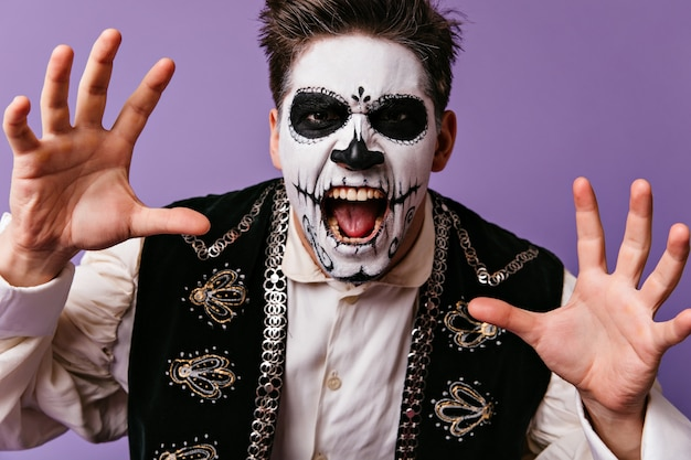 Ciemnowłosy mężczyzna wrzeszczy przerażająco i pozuje na liliowej ścianie. strzał zbliżenie meksykański ze sztuką twarzy.