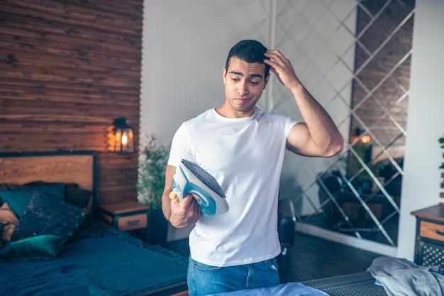 Ciemnowłosy młody mężczyzna w białej koszulce wyglądający na zdezorientowanego trzymający żelazo w dłoni