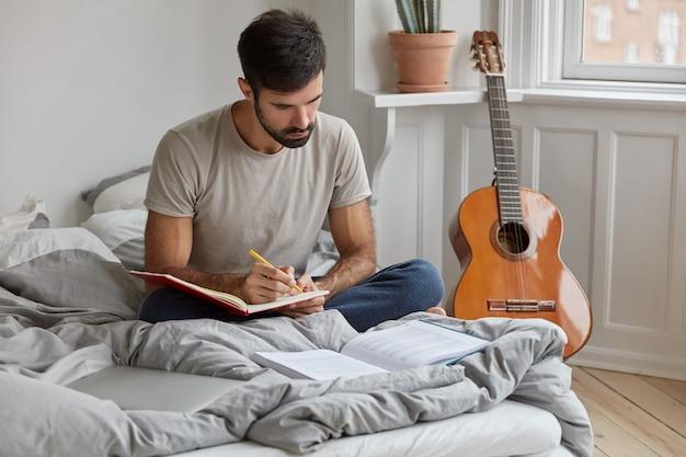 Ciemnowłosy młody mężczyzna w koszulce zapisuje informacje z książki do notesu
