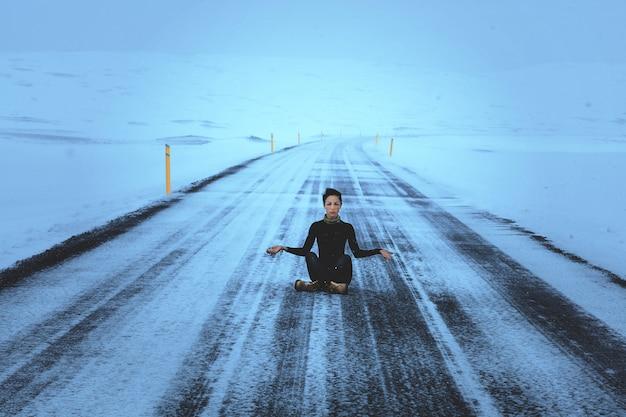 Ciemnowłosy model pozuje siedzącego na drodze