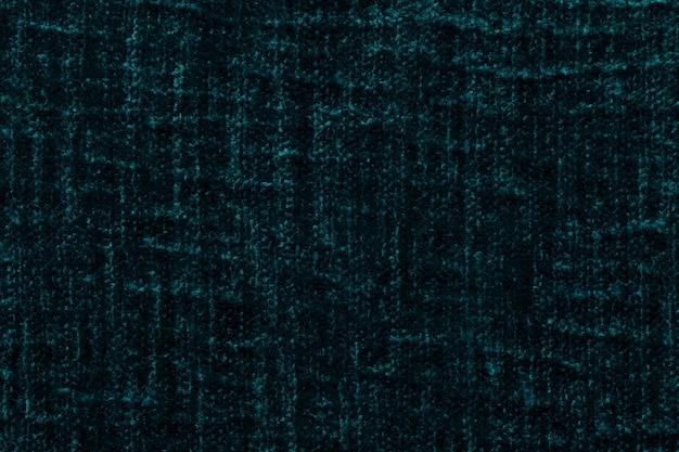 Ciemnozielone puszyste tło z miękkiej, miękkiej tkaniny. tekstura pluszowa owłosiona tkanina, zbliżenie.