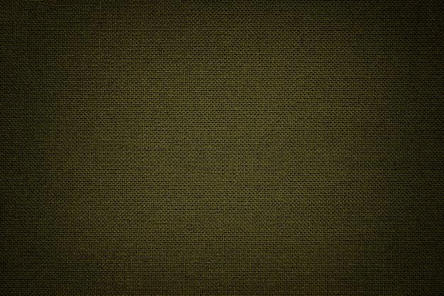 Ciemnozielone tło z materiału tekstylnego. materiał o naturalnej fakturze. zasłona.