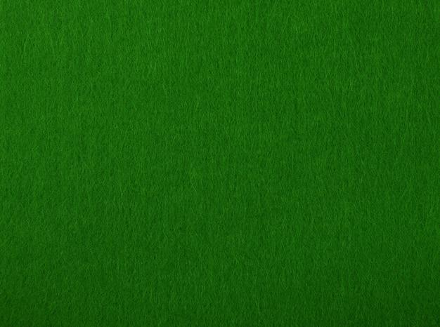 Ciemnozielony stół do pokera czuł miękką szorstką teksturę tła materiału tekstylnego, bliska
