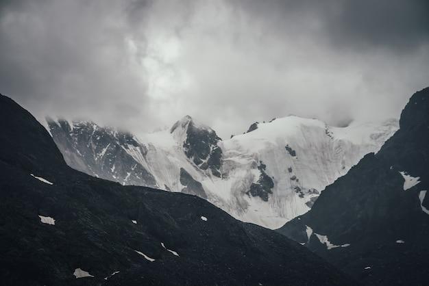 Ciemny atmosferyczny górski krajobraz z lodowcem na czarnych skałach w ołowianym szarym zachmurzonym niebie. ośnieżone góry w niskich chmurach w deszczową pogodę. ponury krajobraz z czarnymi skalistymi górami ze śniegiem we mgle.