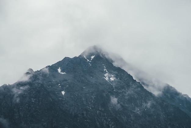 Ciemny atmosferyczny krajobraz z czarnymi sylwetkami gór wśród deszczowych niskich chmur. ponura górska sceneria z deszczowymi chmurami na sylwetce szczytu góry w pochmurną pogodę. szczyt w szarym, zachmurzonym niebie