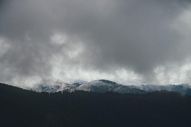 Ciemny atmosferyczny krajobraz z leśnymi górami w śniegu w niskich chmurach w pochmurną pogodę. minimalistyczna ponura sceneria z szarymi chmurami deszczowymi nad ośnieżonymi wzgórzami i górskimi sylwetkami. ziarniste chmury.