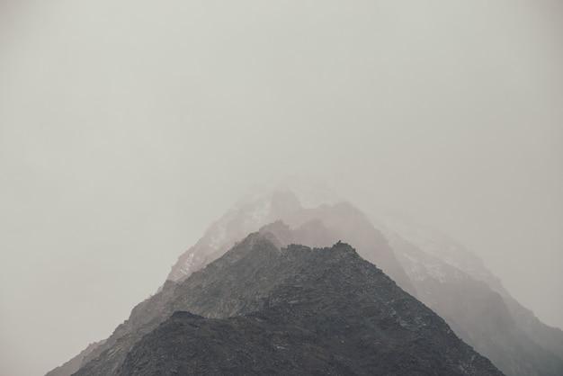 Ciemny atmosferyczny krajobraz z wysokim czarnym skalistym szczytem ze śniegiem w zachmurzonym niebie. dramatyczny górski krajobraz ze szczytem śniegu w mgle przy pochmurnej pogodzie. ponury widok na niesamowite skały we mgle