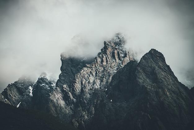 Ciemny atmosferyczny surrealistyczny krajobraz z ciemnym skalistym szczytem w niskich chmurach w szarym pochmurnym niebie. szara niska chmura na wysokim szczycie. wysoka czarna skała ze śniegiem w niskich chmurach. surrealistyczne ponure góry.