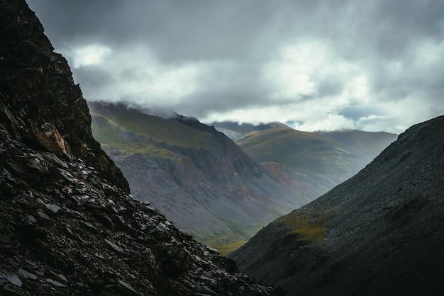 Ciemny, atmosferyczny widok od krawędzi otchłani do zielonej, pstrokatej górskiej doliny w pochmurną pogodę. górski krajobraz z niebezpiecznymi górami i przepaścią pod szarym niebem. przełęcz w deszczową pogodę.