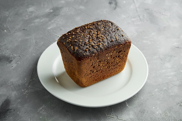 Ciemny chleb żytni w białym talerzu na szarej powierzchni