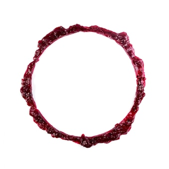 Ciemny czerwony dżem jagodowy okrągłe zmaza ramki lub miejscu na białym tle. słodkie krople konfitury lub marmolada powitalny widok z góry