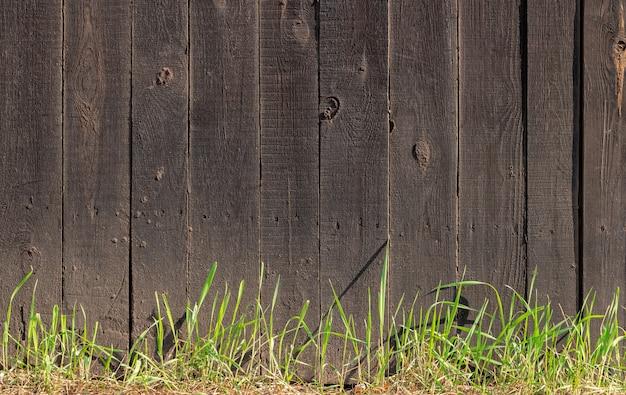 Ciemny drewniany płot z zieloną trawą rosnącą obok niego.