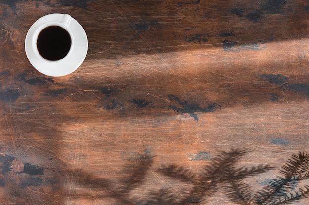 Ciemny drewniany stół biurowy z laptopem i filiżanką kawy. widok z góry i płaskie ułożenie z kopią przestrzeni, zimowe tło