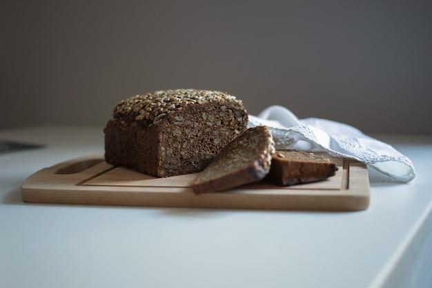 Ciemny i pyszny chleb z nasionami pięknie leży na stole.