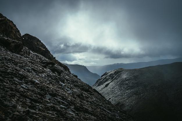 Ciemny, klimatyczny krajobraz na skraju przepaści w górach. niebezpieczne góry i przepaść przy pochmurnej pogodzie. niebezpieczna przełęcz i ostre skały pod szarym niebem. niebezpieczna deszczowa pogoda w górach.