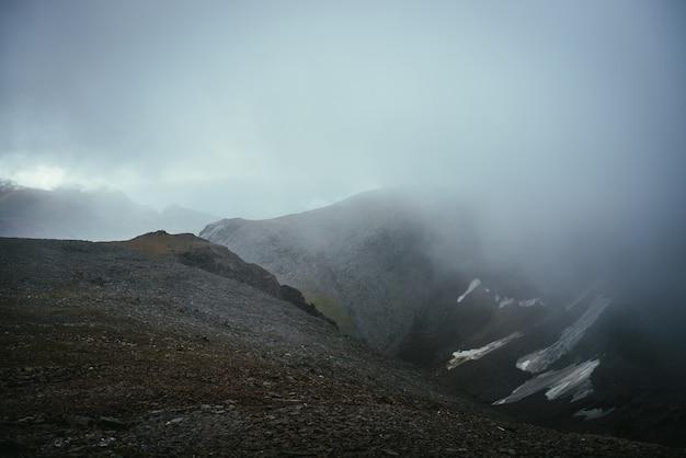 Ciemny, klimatyczny krajobraz na skraju przepaści w górach. niebezpieczne góry i przepaść wśród niskich chmur. niebezpieczeństwo przełęczy i ostre skały w chmurach. niebezpieczna pochmurna deszczowa pogoda w górach.