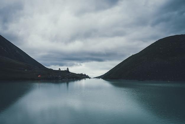 Ciemny krajobraz atmosferyczny z pomarańczowym namiotem w pobliżu górskiego jeziora w dolinie górskiej pod zachmurzonym niebem w ciemności. fale na górskiej wodzie jeziora w zmierzchu. ciemna sceneria z falowaniem wody na górskim jeziorze