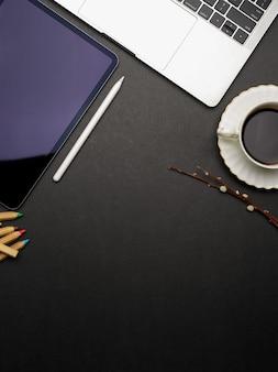 Ciemny, kreatywny, płaski obszar roboczy z tabletem, laptopem, filiżanką kawy i miejscem na kopię, widok z góry