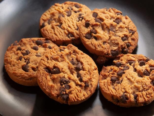 Ciemny matowy talerz z ręcznie robionymi ciasteczkami z kawałkami czekolady