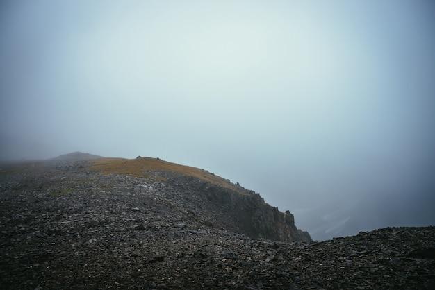 Ciemny, nastrojowy, minimalistyczny mglisty krajobraz na skraju przepaści w górach. niebezpieczne góry i przepaść w gęstej mgle. niebezpieczna przełęcz i ostre skały w gęstej mgle. zerowa widoczność w górach.