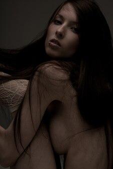 Ciemny nastrojowy obraz pięknej nagiej kobiety.
