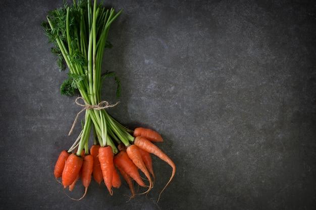 Ciemny nastrojowy obraz żywności świeżej marchewki - fotografia martwa natura. koncepcja czystej żywności