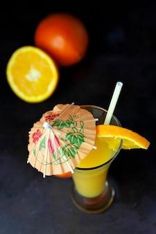 Ciemny naturalny pomarańczowy owoc z widokiem na słomę i parasol