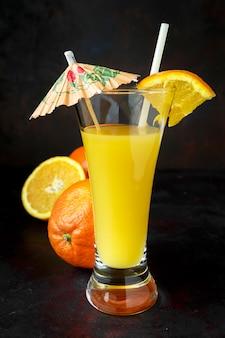 Ciemny naturalny sok pomarańczowy ze słomką i parasolem